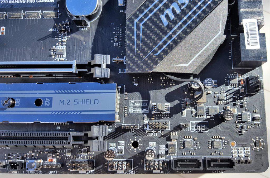 De derecha a izquierda, 2 puertos SATA 3, 2 conectores USB 2.0 para dos puertos cada uno y los conectores del panel frontal. A la derecha del M.2 Shield también tenemos el conector de intrusión de chasis (JCI1) y el chip de BIOS. También tenemos diagrama de conexión del frontal, por si perdemos el manual.